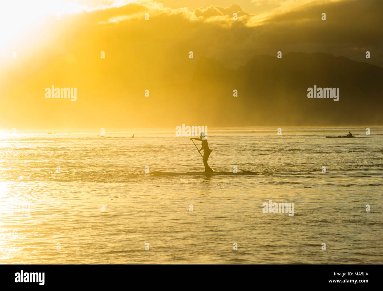 Stand up paddlers  working out at sunset with Moorea in the background, Papeete, Tahiti, French Polynesia - Stock Image