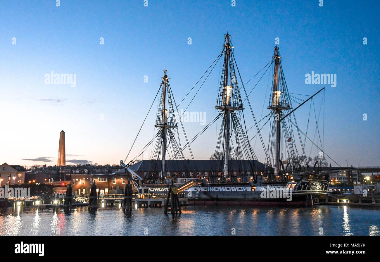 The U.S.S. Constitution, which fought in the American Revolution, docked in Boston Harbor with the Bunker Hill Monument in the background at sunset. - Stock Image