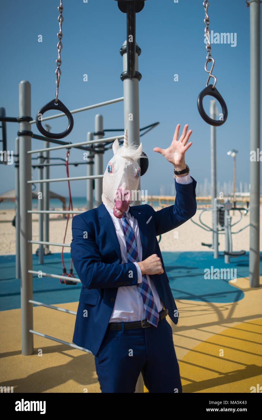 Unusual trainer in suit and mask welcomes you at sport ground. Strange man ready to pump the muscles. Freaky unicorn is engaged in fitness outdoors - Stock Image