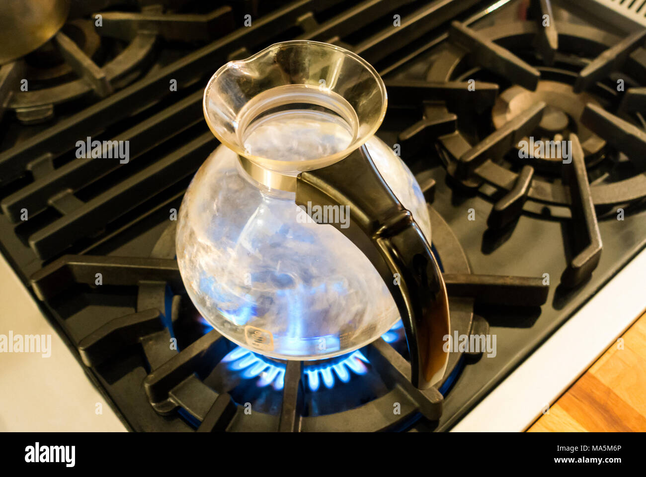 Water boiling in a One All glass Whistling Kettle by Medelco on a stovetop - Stock Image