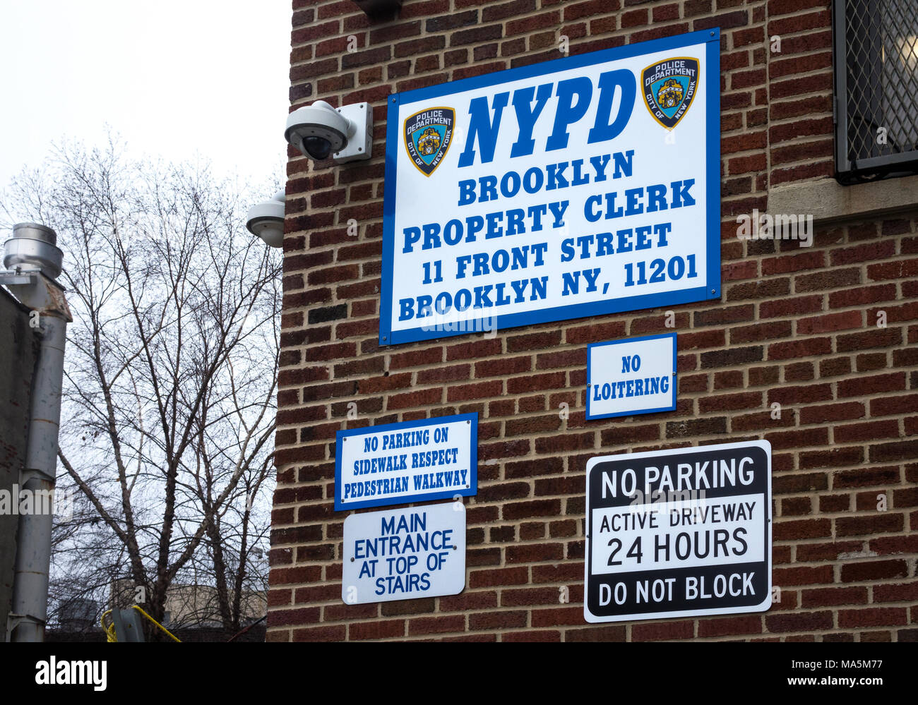 NYPD Brooklyn Property Clerk HQ building, with warning signs on an outside wall - Stock Image