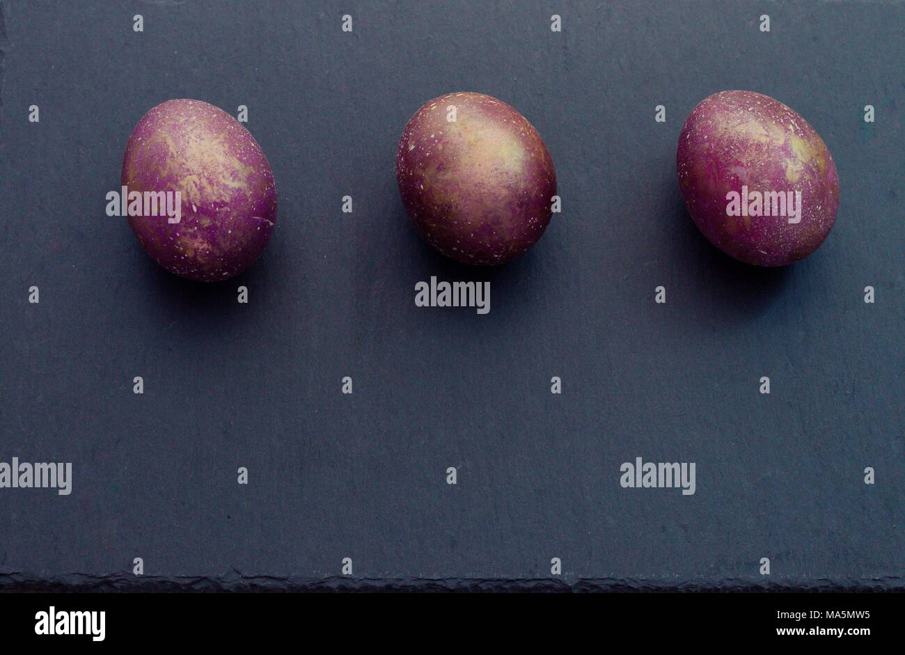 66bd40a054d1 Fantasy cosmic marble purple golden easter three eggs on slate cutting  board black background. Top view. Copyspace