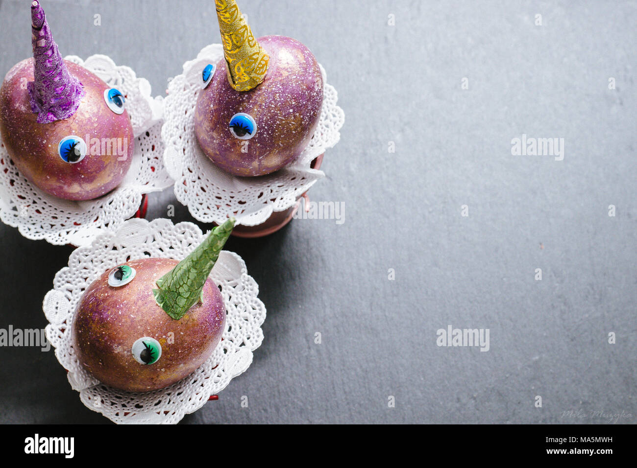 6b1b092d65a1 Easter cosmic purple and gold crafted eggs unicorns with eyes and colorful  patterned horns on slate background with lace napkins. Copyspace. Top view