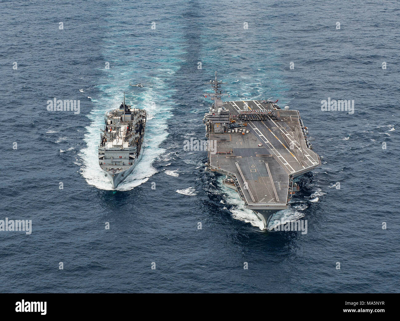 180327-N-JC445-0399 ATLANTIC OCEAN (March 27, 2018) The fast combat support ship USNS Supply (T-AOE 6) sails alongside the aircraft carrier USS George H.W. Bush (CVN 77) during a replenishment-at-sea. The ship is underway conducting sustainment exercises to maintain carrier readiness. (U.S. Navy photo by Mass Communication Specialist 3rd Class Mario Coto) - Stock Image