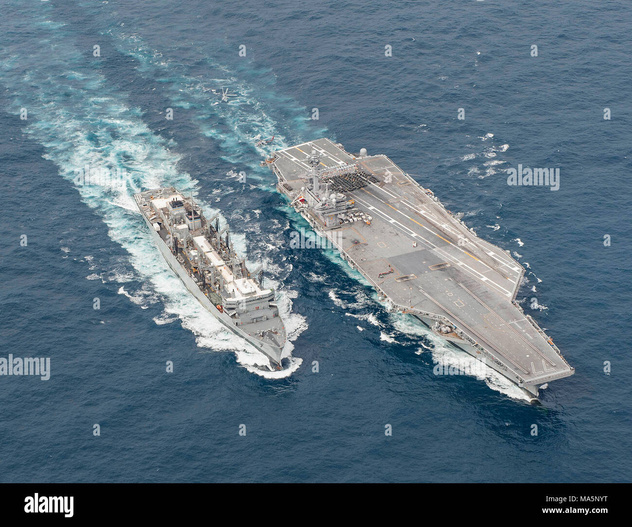 180327-N-JC445-0547 ATLANTIC OCEAN (March 27, 2018) The fast combat support ship USNS Supply (T-AOE 6) sails alongside the aircraft carrier USS George H.W. Bush (CVN 77) during a replenishment-at-sea. The ship is underway conducting sustainment exercises to maintain carrier readiness. (U.S. Navy photo by Mass Communication Specialist 3rd Class Mario Coto) - Stock Image