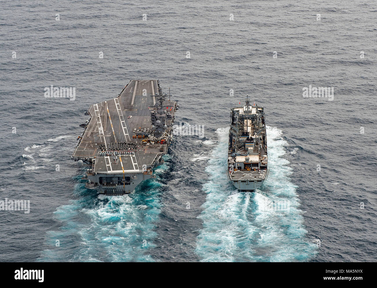 180327-N-JC445-0413 ATLANTIC OCEAN (March 27, 2018) The fast combat support ship USNS Supply (T-AOE 6) sails alongside the aircraft carrier USS George H.W. Bush (CVN 77) during a replenishment-at-sea. The ship is underway conducting sustainment exercises to maintain carrier readiness. (U.S. Navy photo by Mass Communication Specialist 3rd Class Mario Coto) - Stock Image
