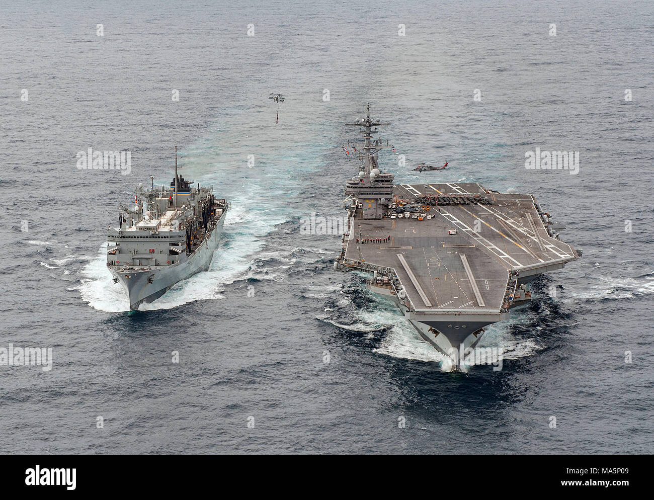 180327-N-JC445-0575 ATLANTIC OCEAN (March 27, 2018) The fast combat support ship USNS Supply (T-AOE 6) sails alongside the aircraft carrier USS George H.W. Bush (CVN 77) during a replenishment-at-sea. The ship is underway conducting sustainment exercises to maintain carrier readiness. (U.S. Navy photo by Mass Communication Specialist 3rd Class Mario Coto) - Stock Image