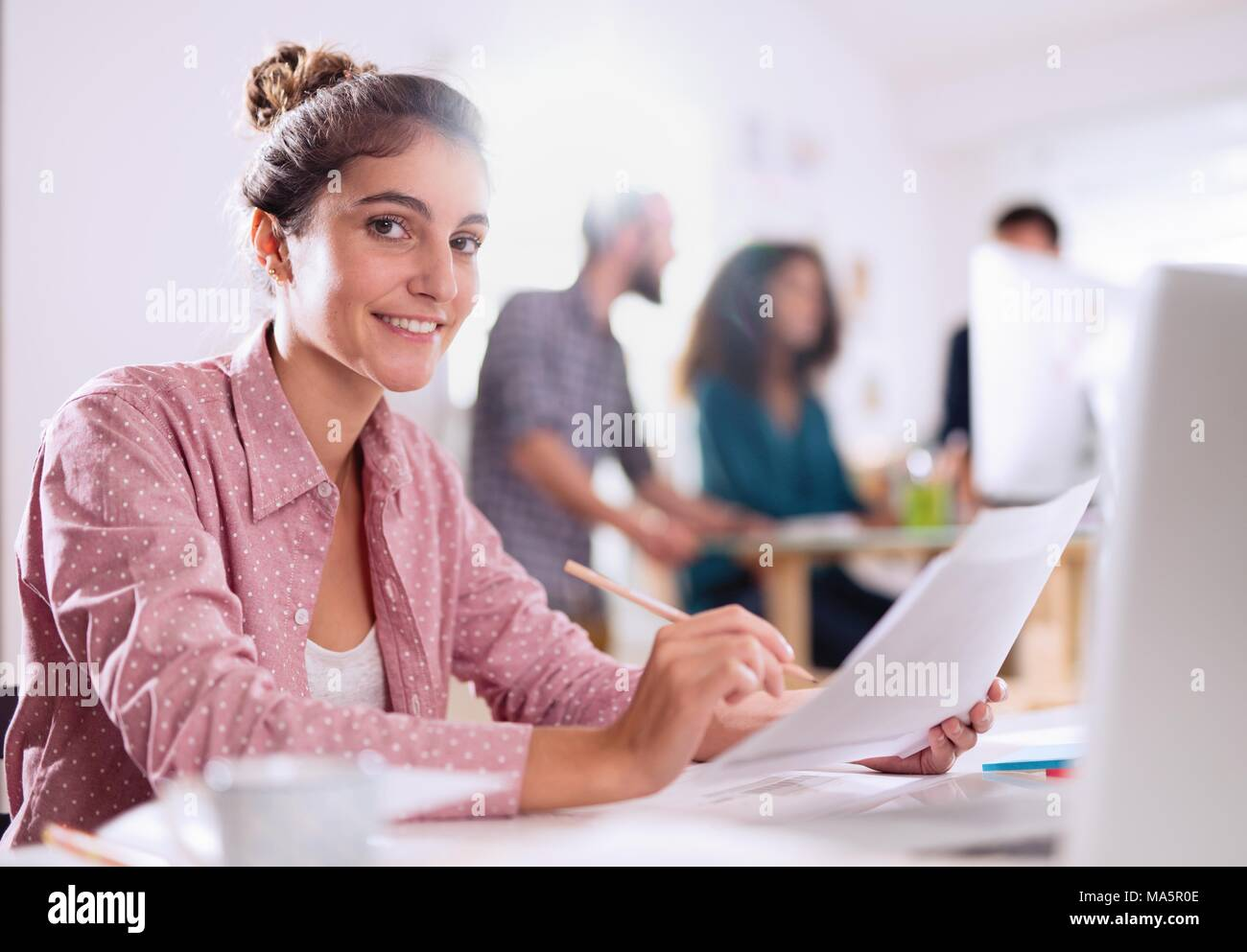 Young work team working in an office - Stock Image