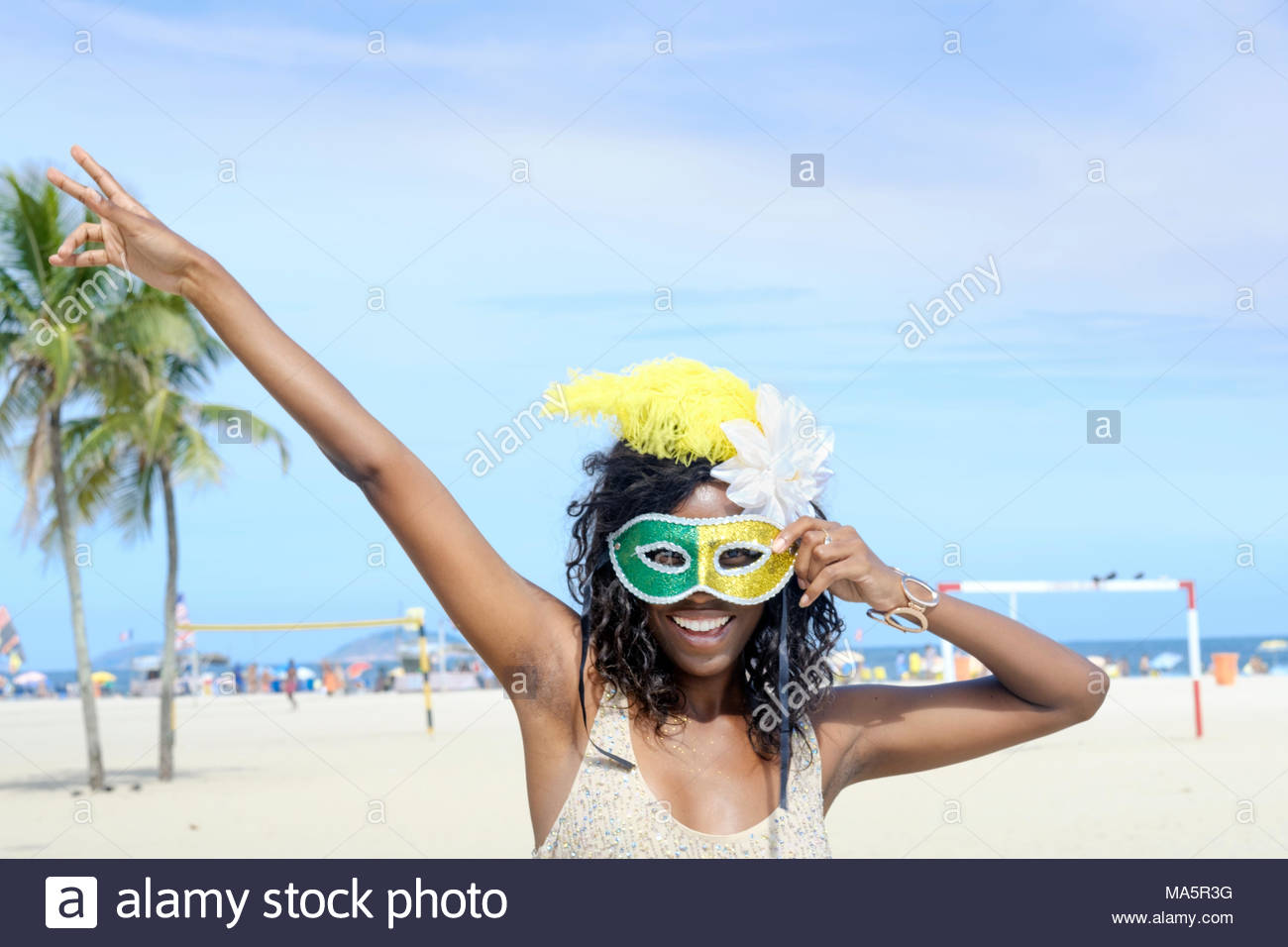 A young African Brazilian woman on the beach, wearing a carnival mask and feathers - Stock Image
