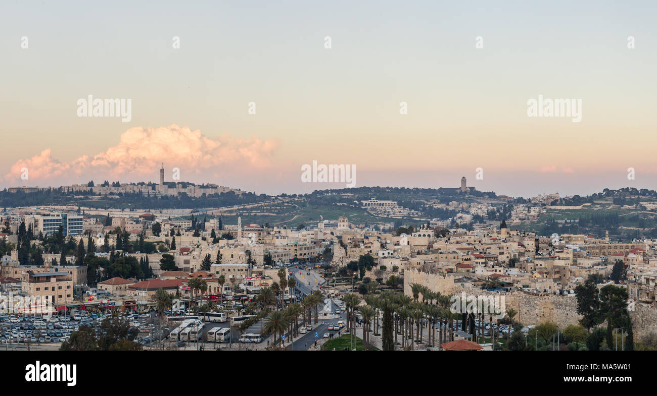 A sunset view of the holy city of Jersualem in Israel, with a view of the Dome of the Rock, The Temple Mount, The Mount of Olives, and the Old City - Stock Image