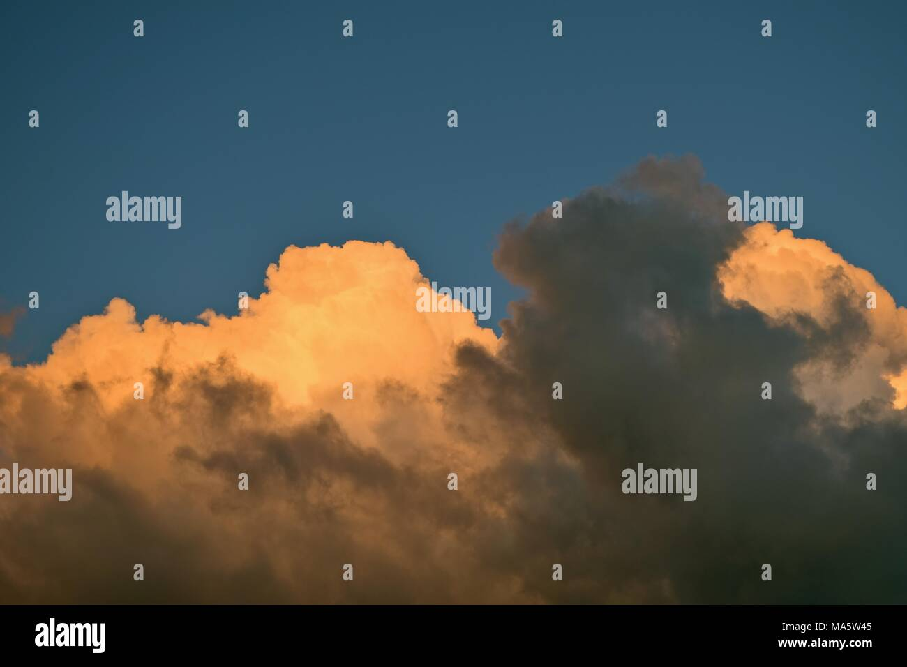 Stormy clouds are blowing in at dusk turning the skies dark. - Stock Image