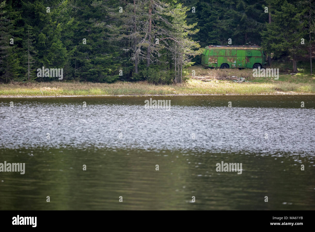 Old rusty bus turned into a storage room in the pine tree forest at the shore of the lake of Shiroka Polyana in Rhodope mountain, Bulgaria - Stock Image
