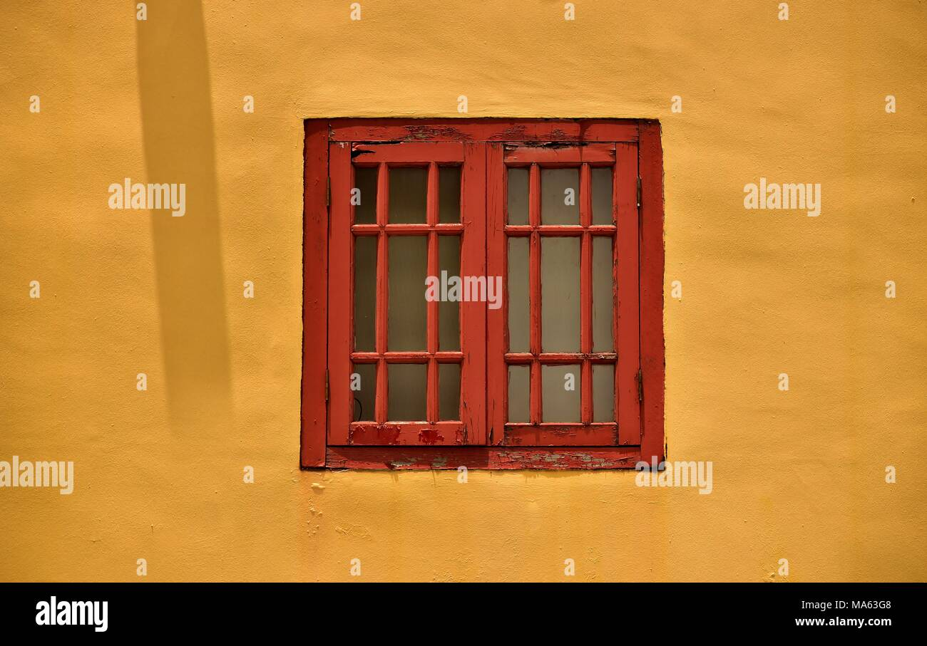 Antique red wooden window isolated against a vintage yellow wall of a traditional Singapore shophouse in historic Chinatown with space for copy Stock Photo