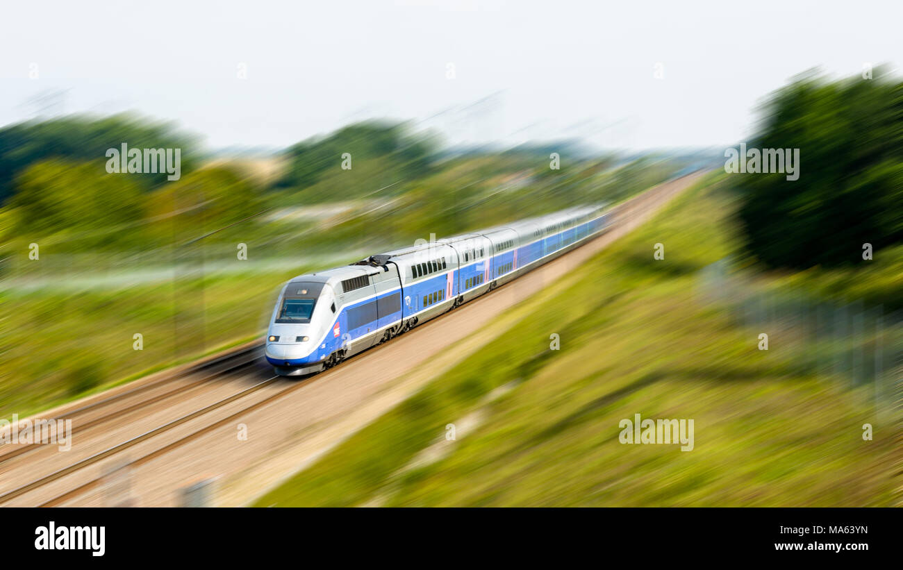 A double-decker high-speed TGV Duplex train in Atlantic livery, operated by french company SNCF, driving to Paris at full speed in the countryside. - Stock Image