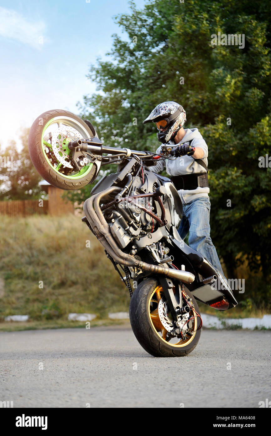 Ivano-Frankivsk, Ukraine - 28 August 2015 : Confident biker performing extreme stunts on sport motorcycle . Man stands on one backwheel of bike on the road near green trees on background.. Stock Photo
