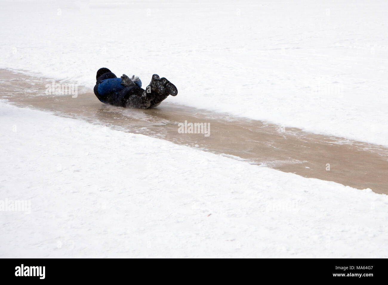 Risk of accidents in winter - A woman slipped on a snow slippery road - Stock Image