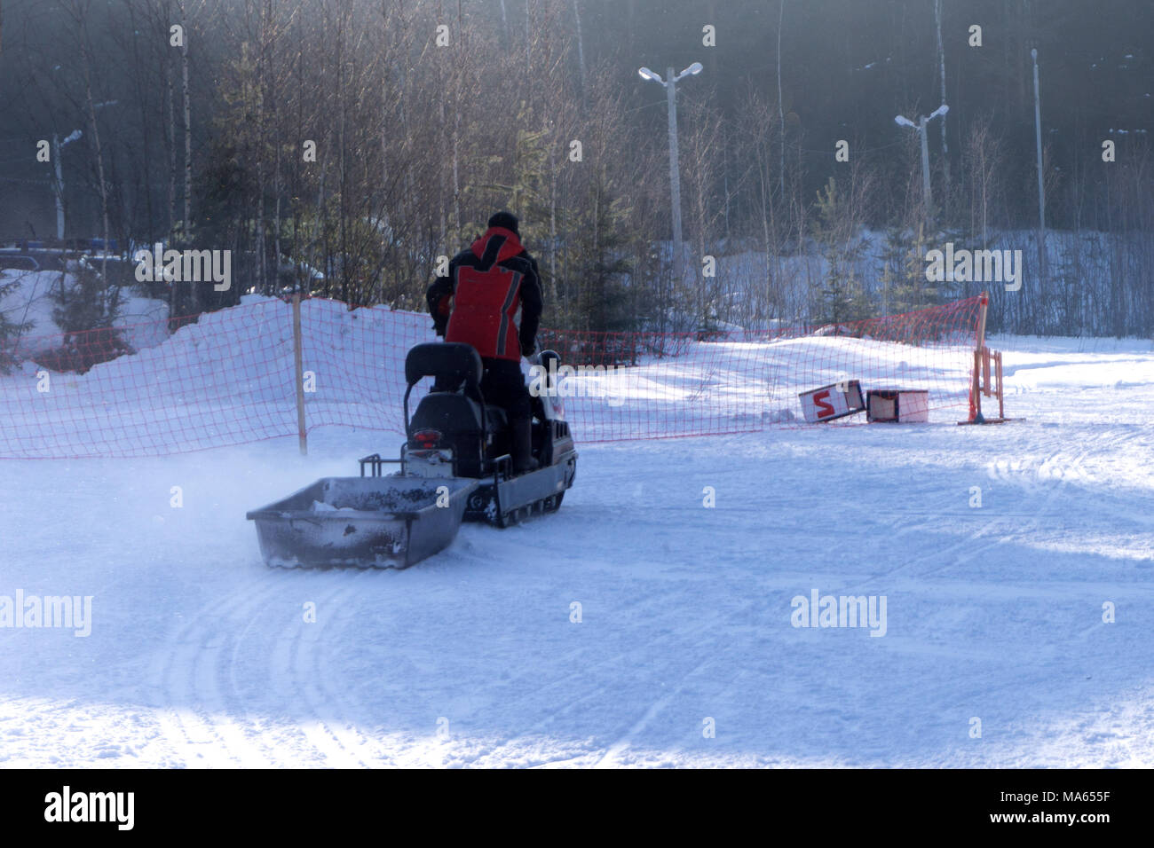 Man driving sports snowmobile in Finnish Lapland in a sunny day - Stock Image