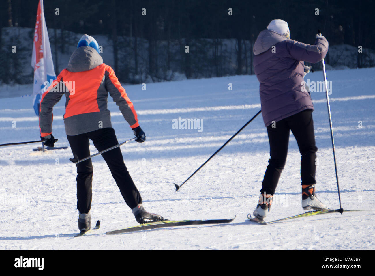 Woman and man skiers in blue suits and helmets prepare for slope at winter in snowy mountains - Stock Image