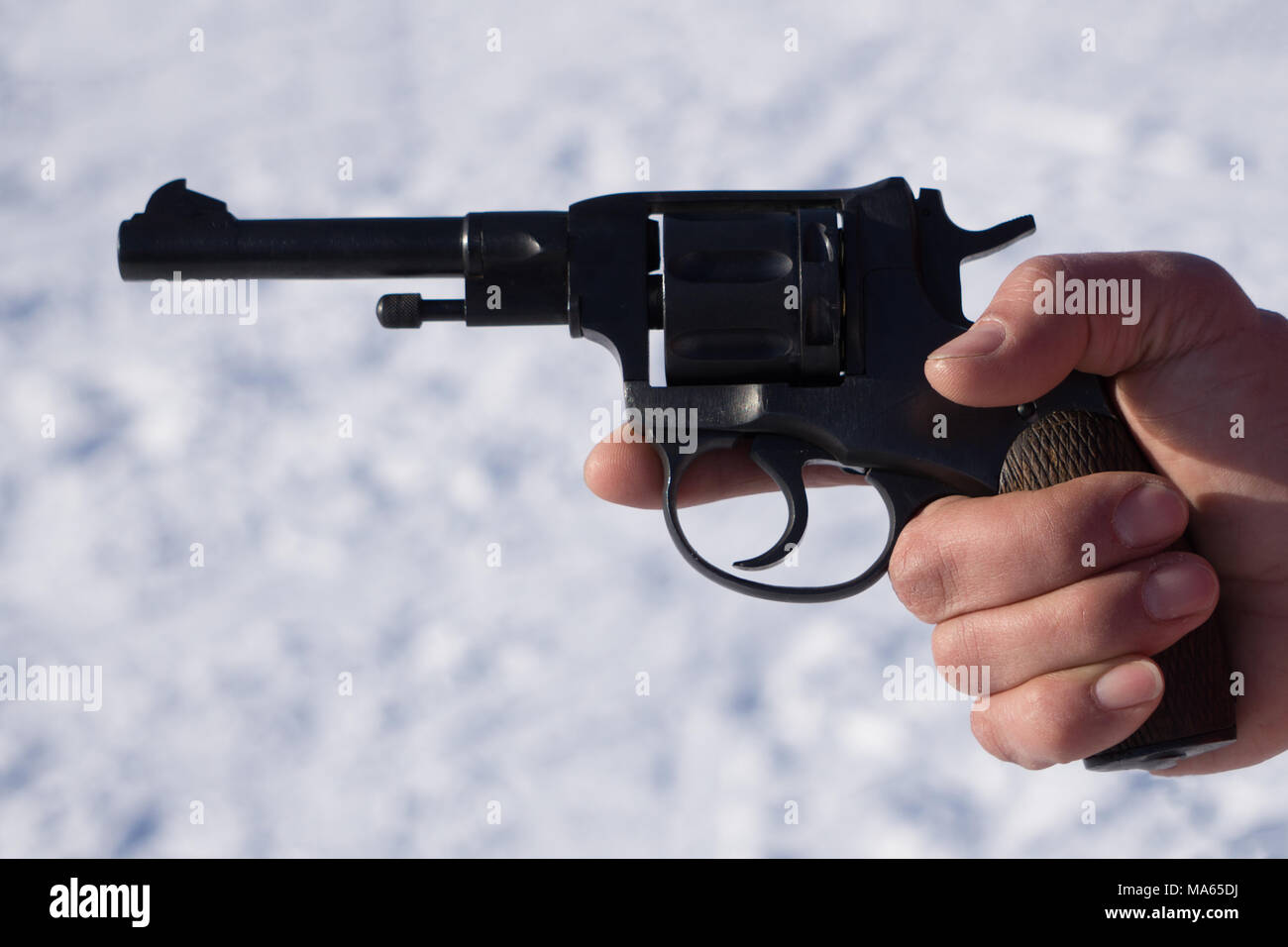 Men hand with revolver pistol isolated on a white background - Stock Image