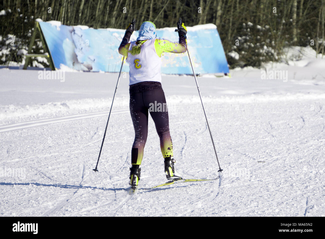 Skier on ski runs downhill in a beautiful Blue sky on background. Free space for text - Stock Image