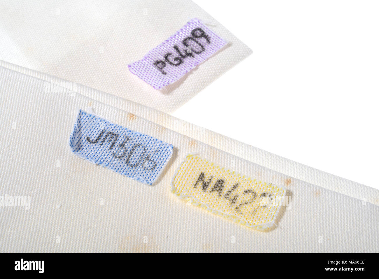 Old fashioned laundry tags to denote where items of laundry should be returned to. - Stock Image