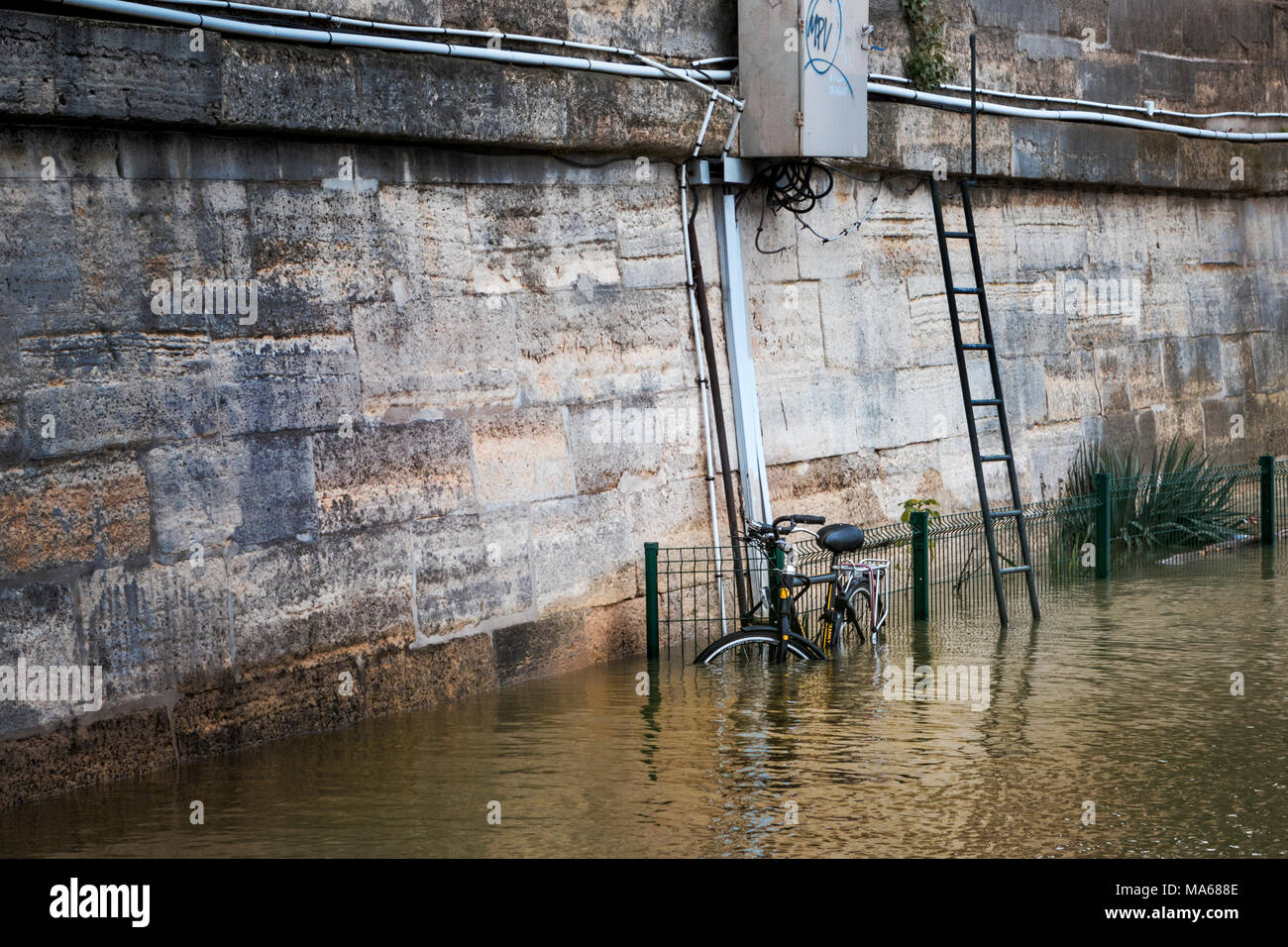Bicycle secured to fencing submerged on a sunken pathway in the swollen river Seine during the 2018 flood of Paris - Stock Image