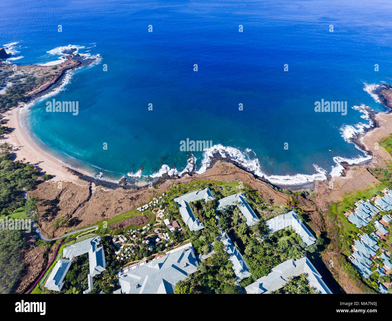 An aerial view of the golden beach and palm tree's at Hulopo'e Beach Park, and the Four Seasons resort at Manele Bay, Lanai Island, Hawaii, USA. Stock Photo