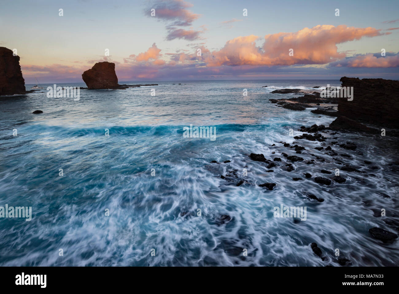 """Sunset light on the clouds above Puu Pehe Rock, also known as """"Sweetheart Rock"""", one of Lanai's most recognizable landmarks, Lanai Island, Hawaii, USA - Stock Image"""