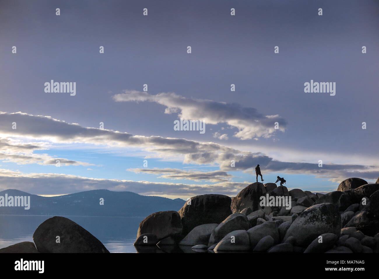 Silhouettes of two people walking on rocks at Lake Tahoe USA - Stock Image