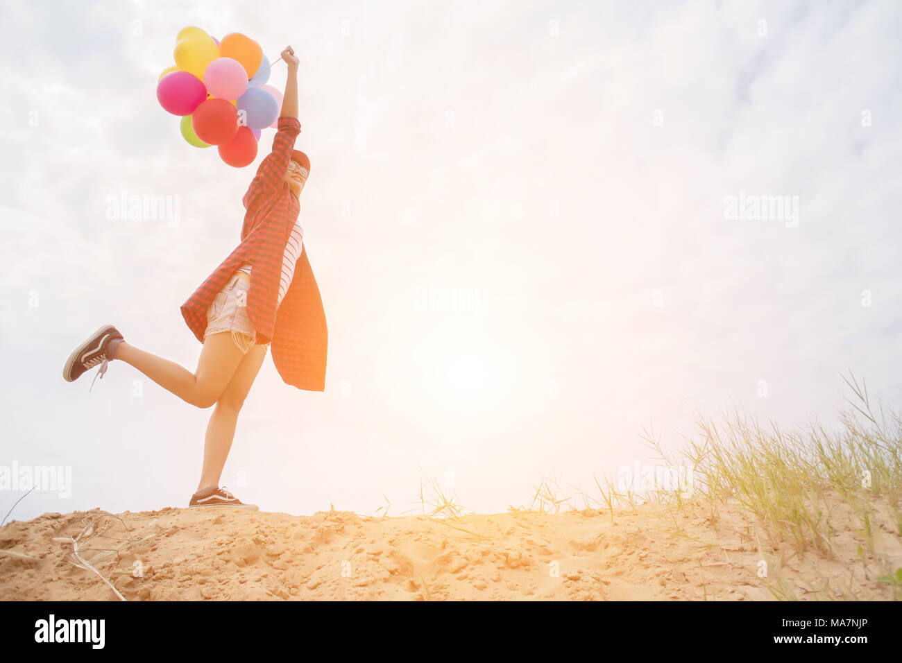Teenage girls holding colorful balloons in the bright sky and smiled happily. - Stock Image