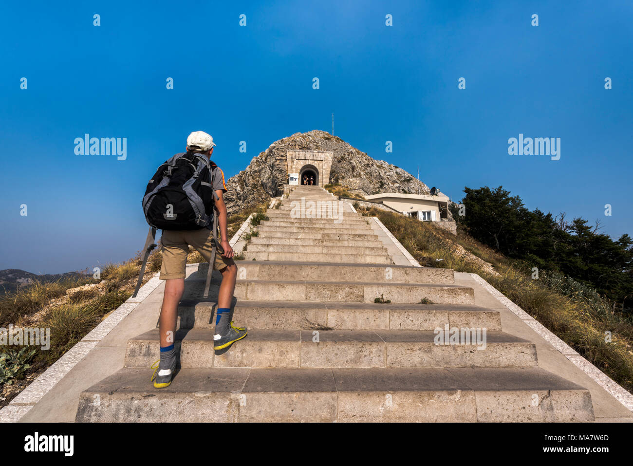 Njegusi mausoleum in Lovcen National Park - Young tourist boy  with backpack climbing the steep stairs to the entrance Stock Photo