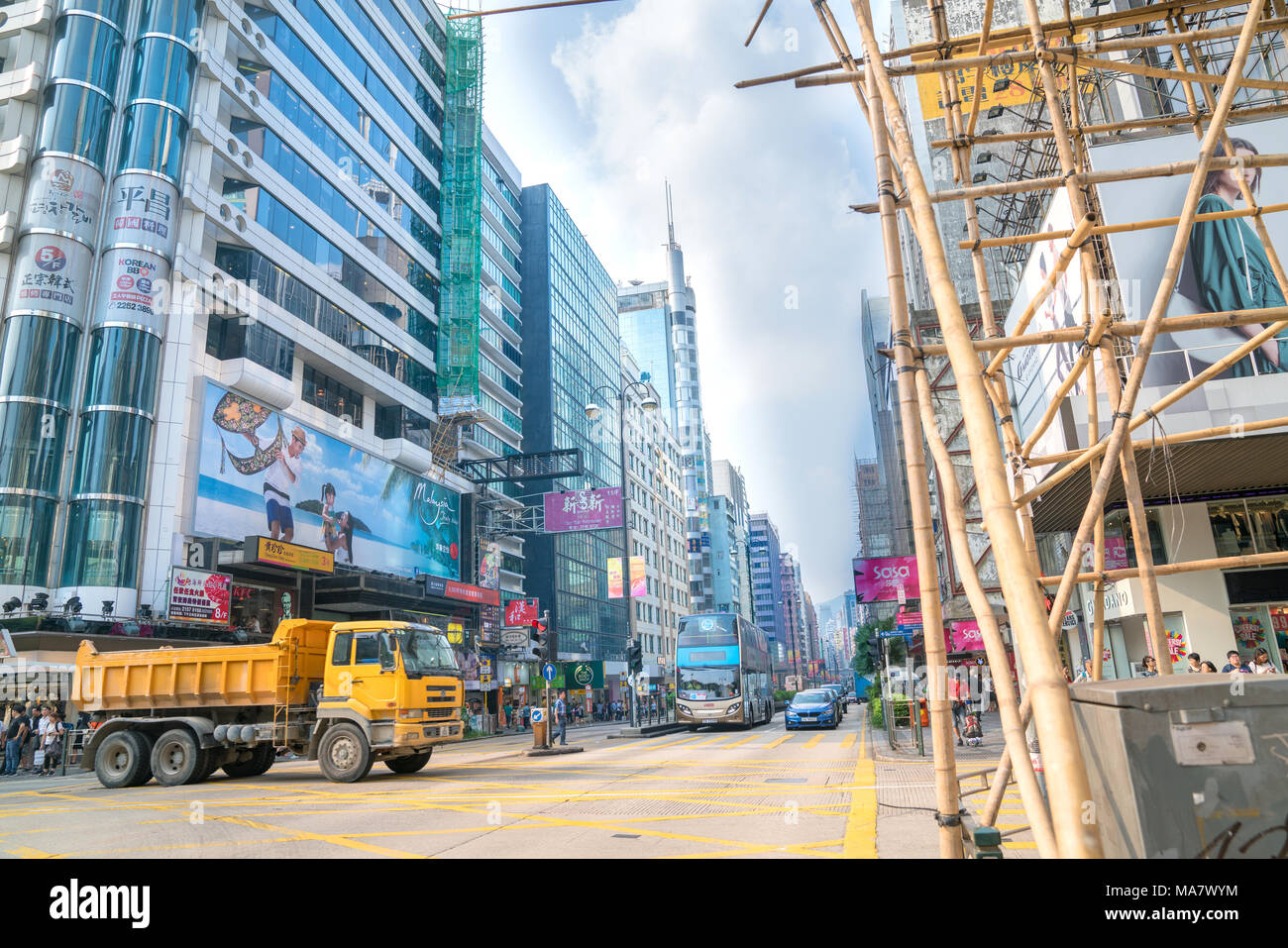 KOWLOON, HONG KONG - SEPTEMBER 18 2017; Typically Asian downtown city street  scene with modern buildings on one side bamboo scaffolding across street - Stock Image