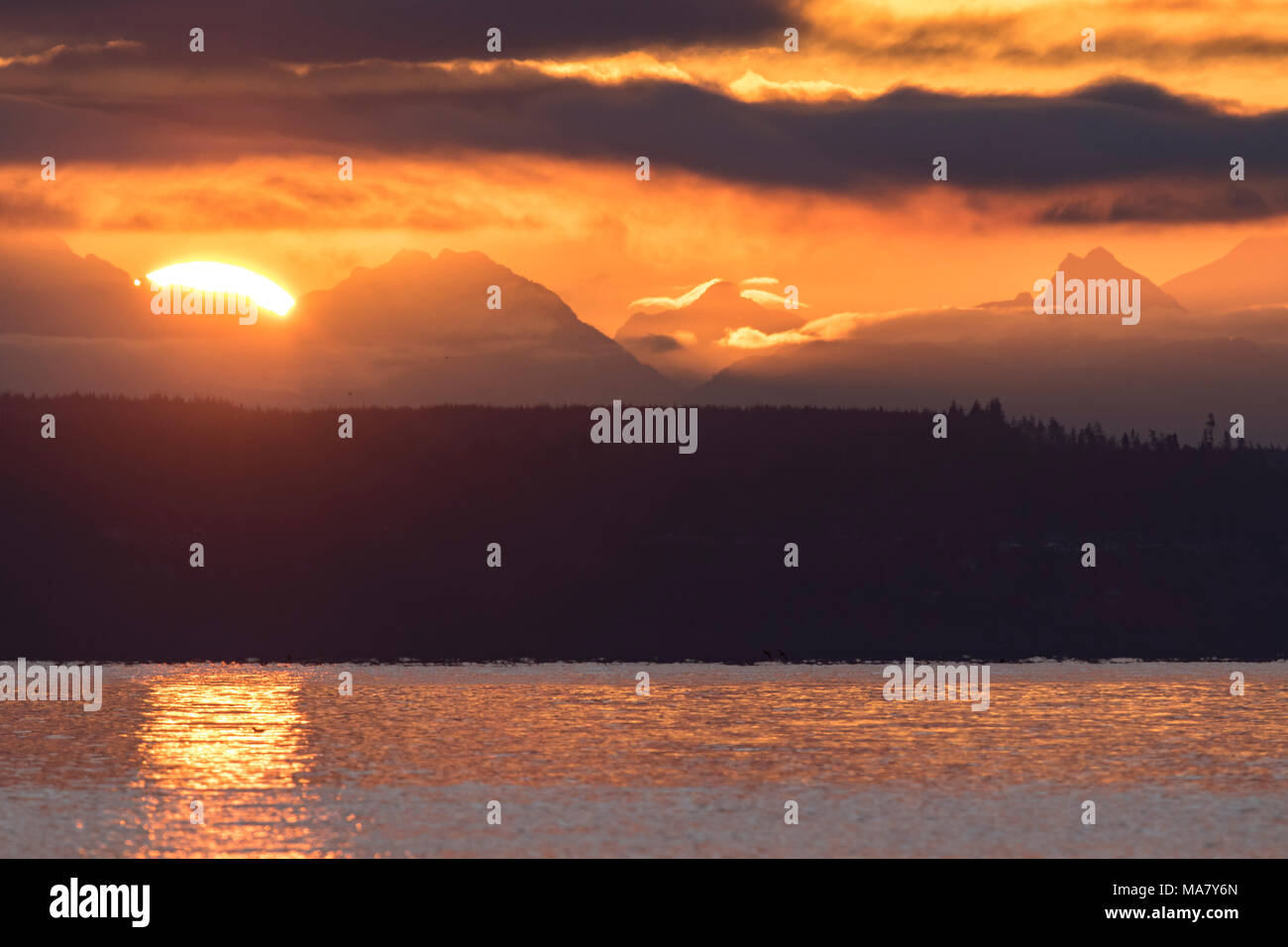 Sunrise, sun rise, over mountains. Sunset mountains panoramic. Colorful and scenic sunrise over the Cascade Mountains. From Port Townsend. - Stock Image