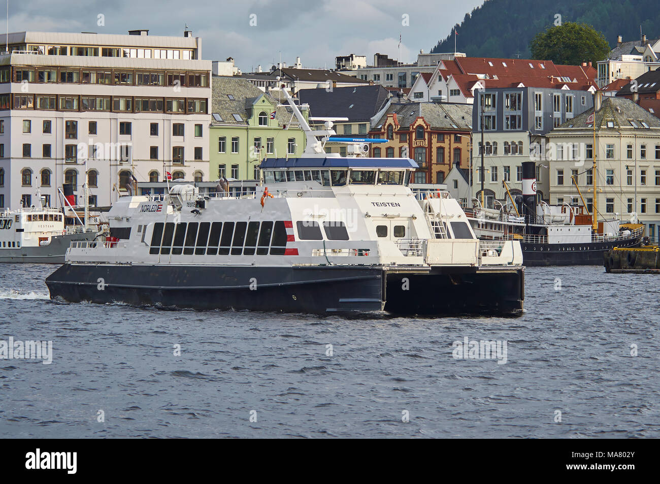 One of the small Coastal Passenger Ferries, The Teisten, makes its way out of Bergen full of passengers for one of its Coastal Stops - Stock Image