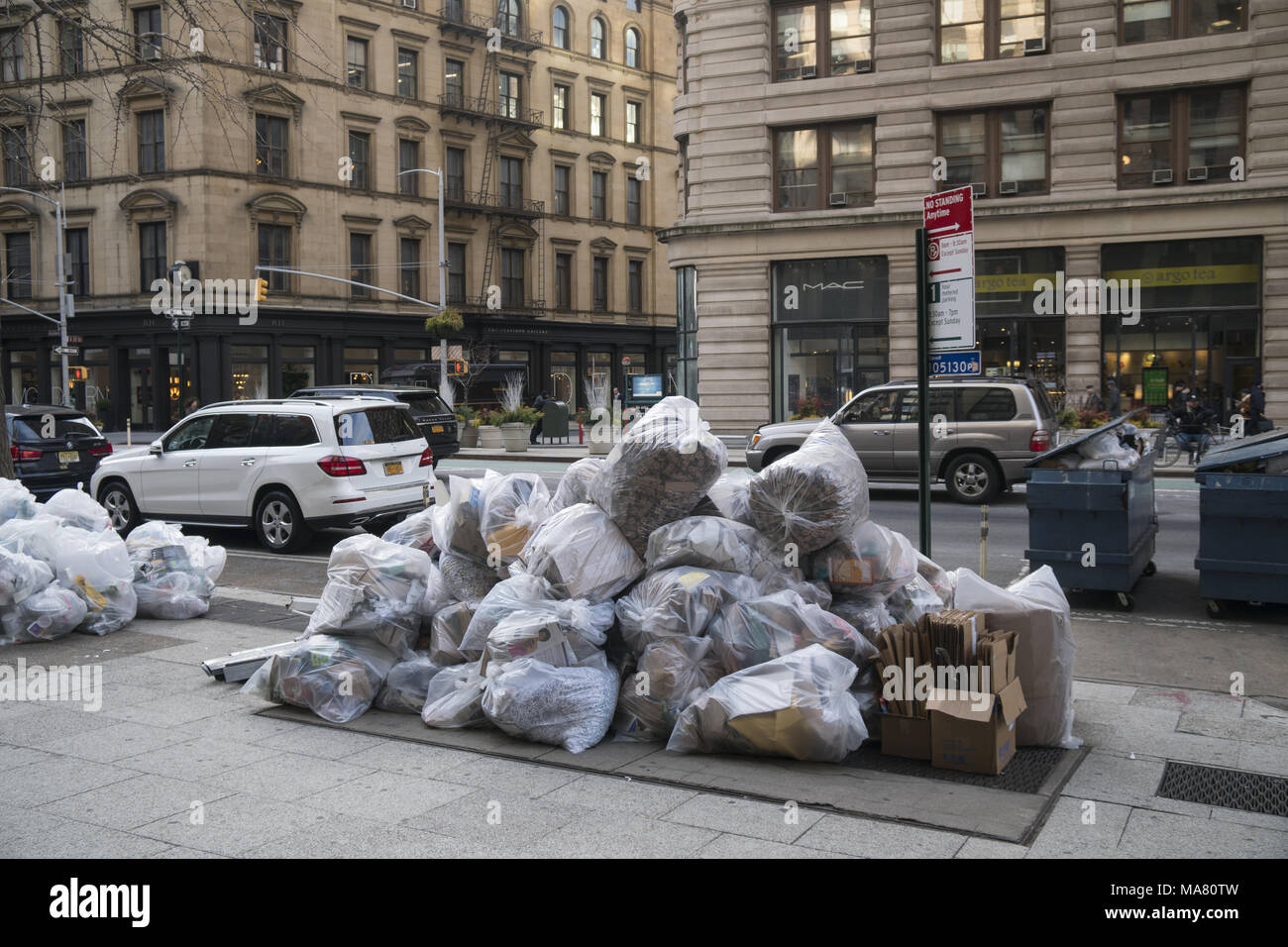 Clear bagged recyclable garbage on the street ready for pick-up on Broadway by the landmark Flatiron Building. Manhattan has virtually no alleys so most garbage is put out on the street. (Very unsightly) - Stock Image