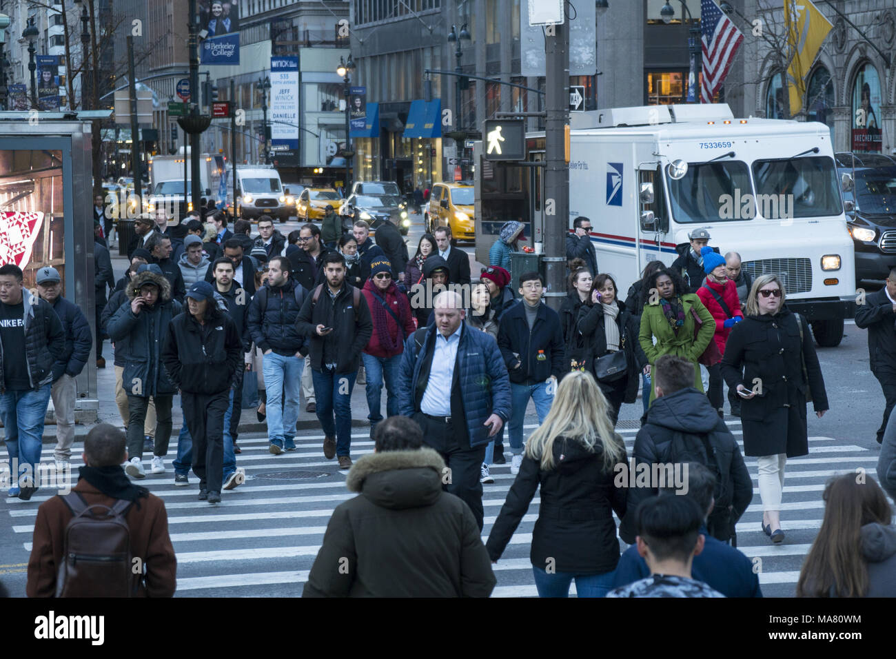 Pedestrians in the crosswalk at the always busy corner of 5th Avenue and 42nd Street in midtown Manhattan, NYC. - Stock Image