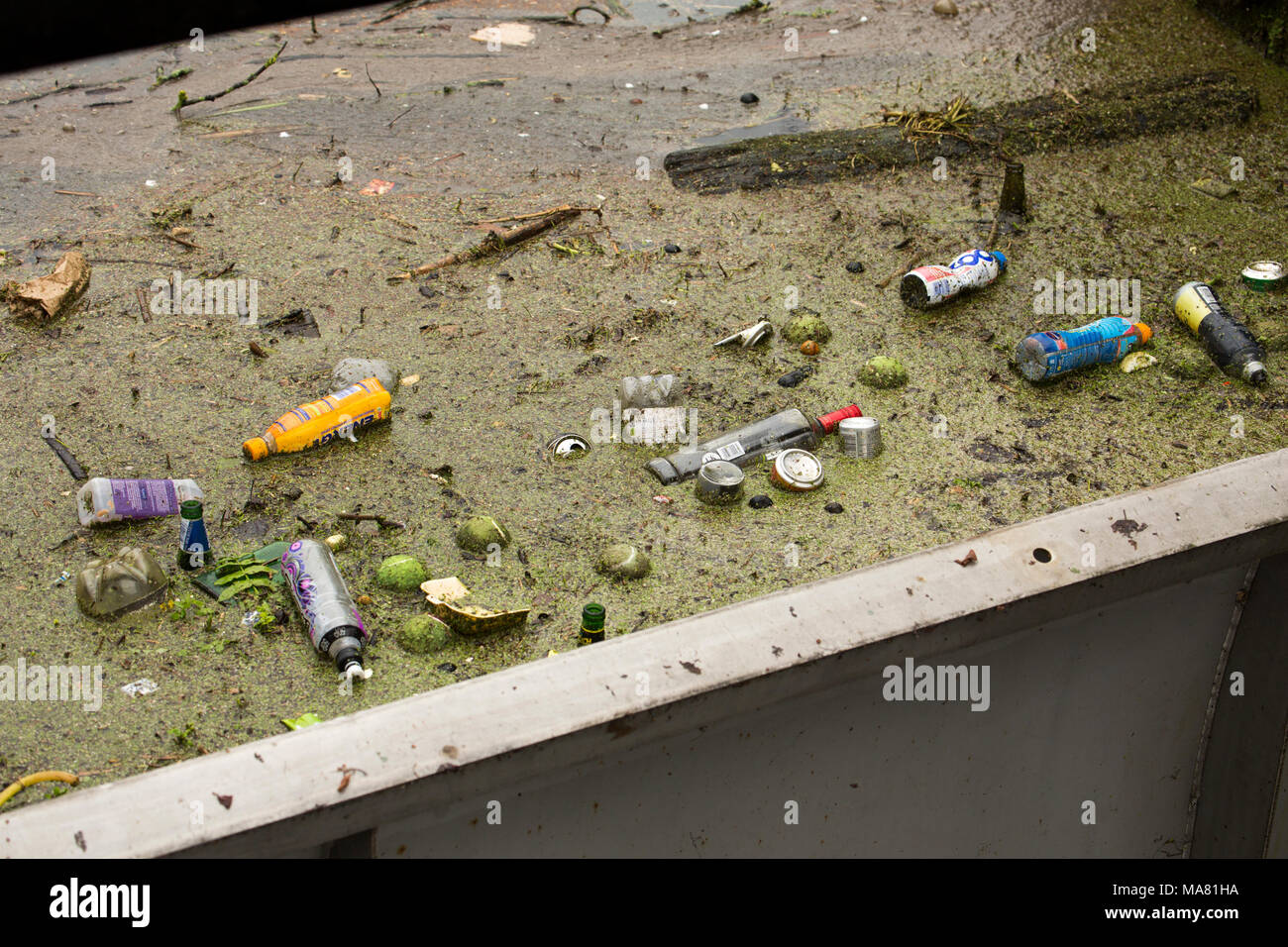 Plastic bottles, tennis balls and other rubbish accumulating about a sluice gate, River Avon Salisbury Wiltshire England UK - Stock Image