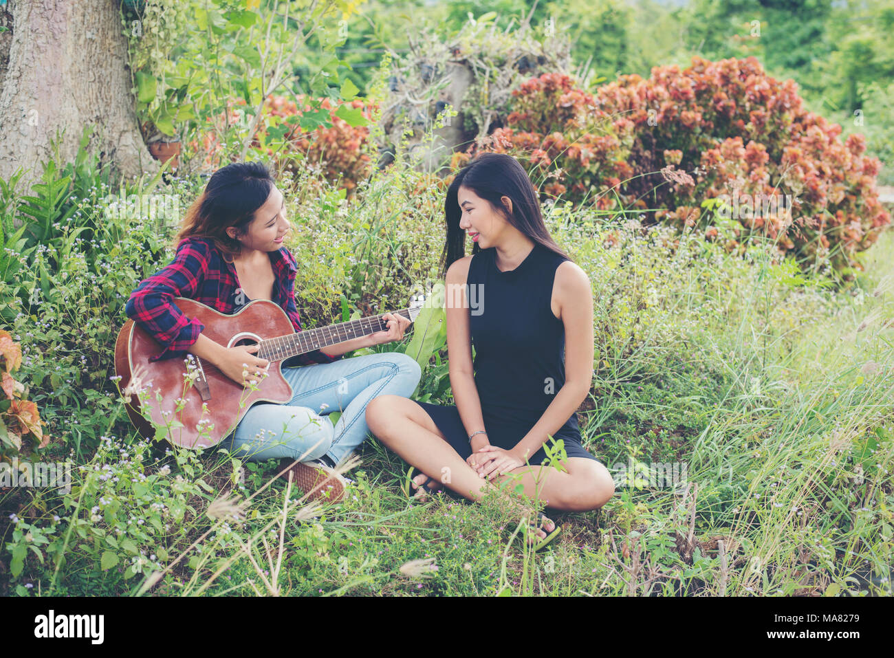 Young teenage looking at her female friend while playing guitar,Relaxing time enjoyment. - Stock Image