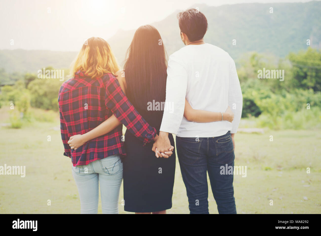 Love triangle, Man is hugging a woman and he is holding hands with another girl,standing outdoor in the park. - Stock Image