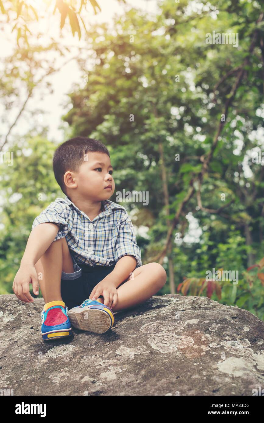 Little Boy Sitting On Rock Stock Photos & Little Boy