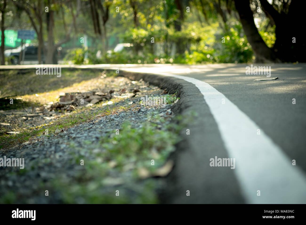 Curve way running and walkway aphalt floor in public park, shot with low depth of field, selective focus. - Stock Image