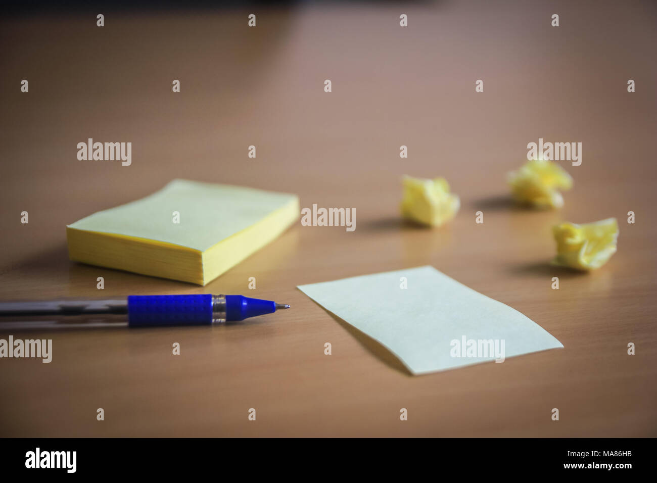 collection of pins and note paper bunch and loose papers on wooden board. ball point pen. side view ready to fill your text and design quotes. - Stock Image