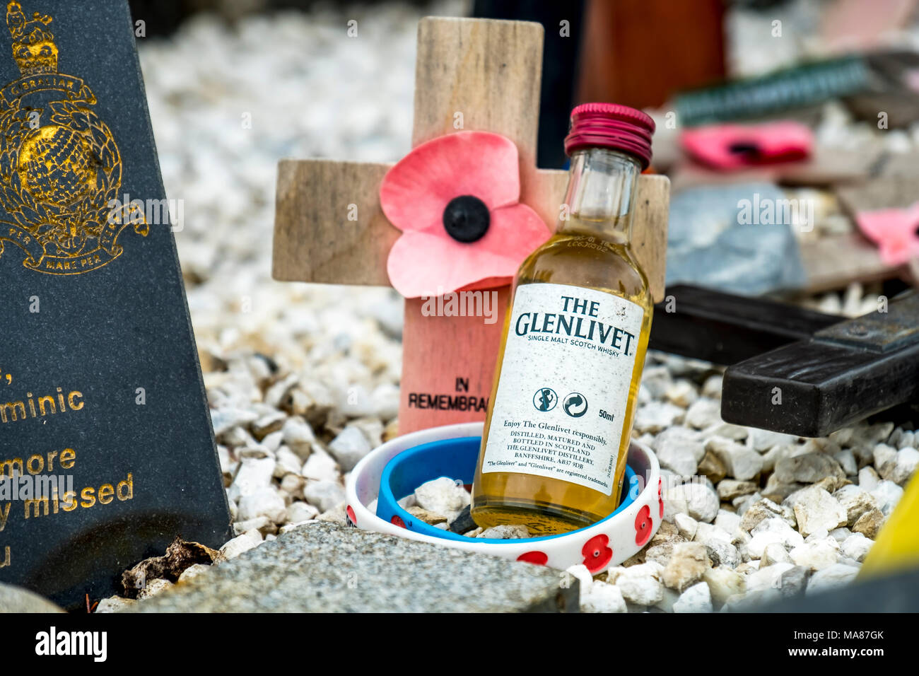 SPEAN BRIDGE / SCOTLAND - MAY 31 2017 : Memorial place for the fallen with poppies, crosses and a whisky bottle. Stock Photo