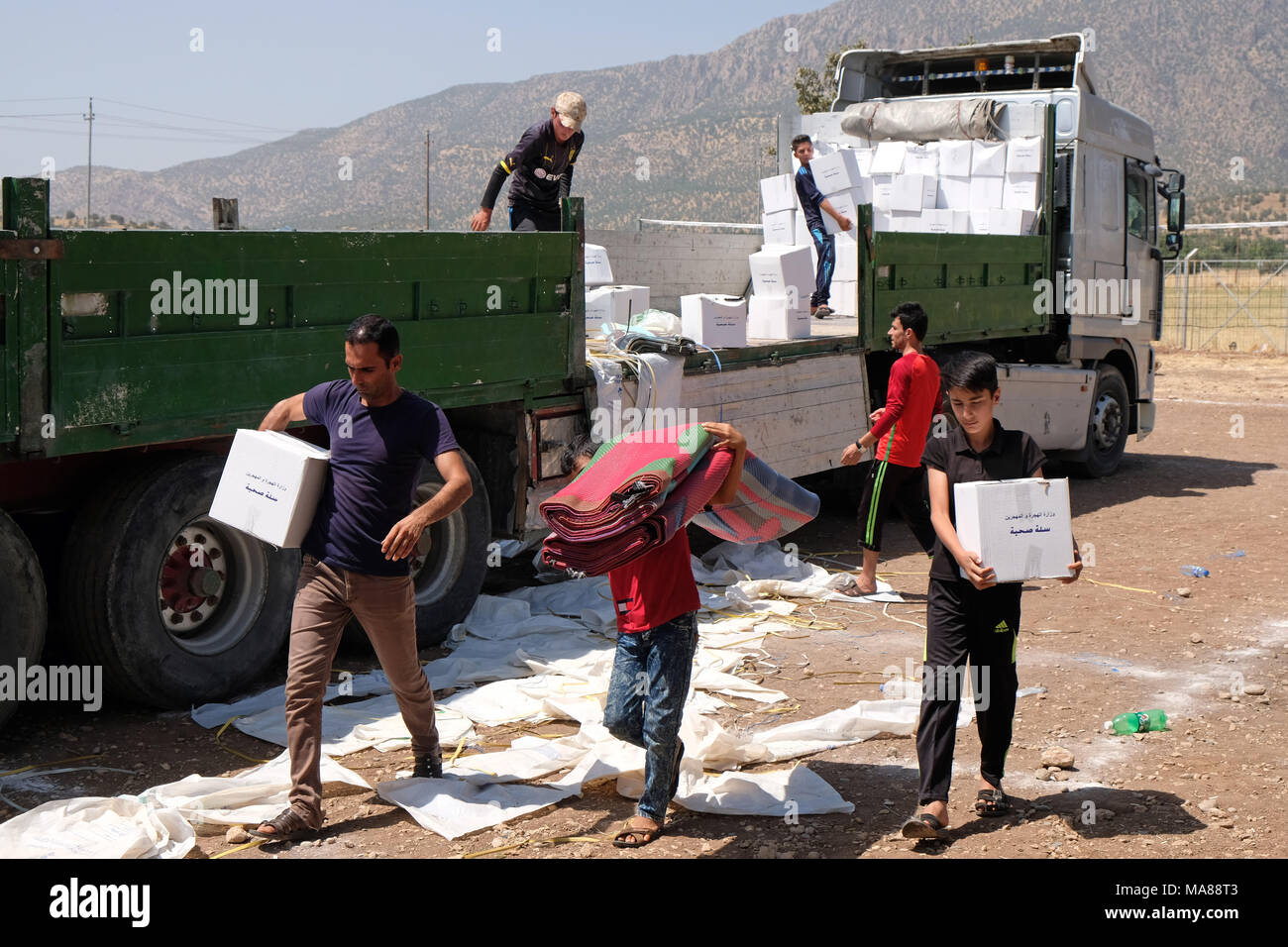 Northern Iraq, Kurdish Autonomous Region: Relief supplies are distributed in the Dawidiya Camp for Yezidi IDPs from the Sinjar Mountains - Stock Image