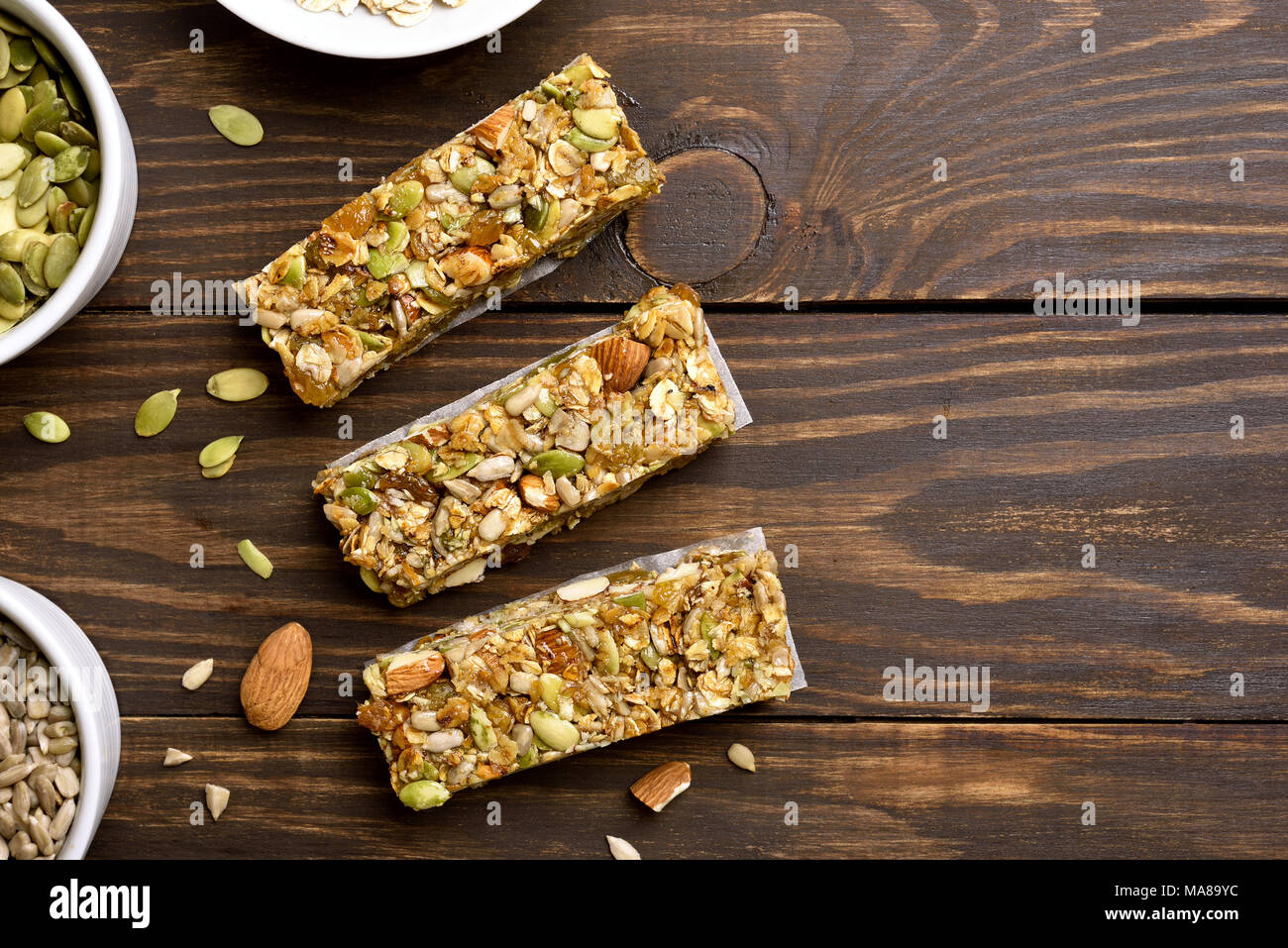 No baked granola bar on wooden background with copy space. Energy natural snack. Top view, flat lay - Stock Image