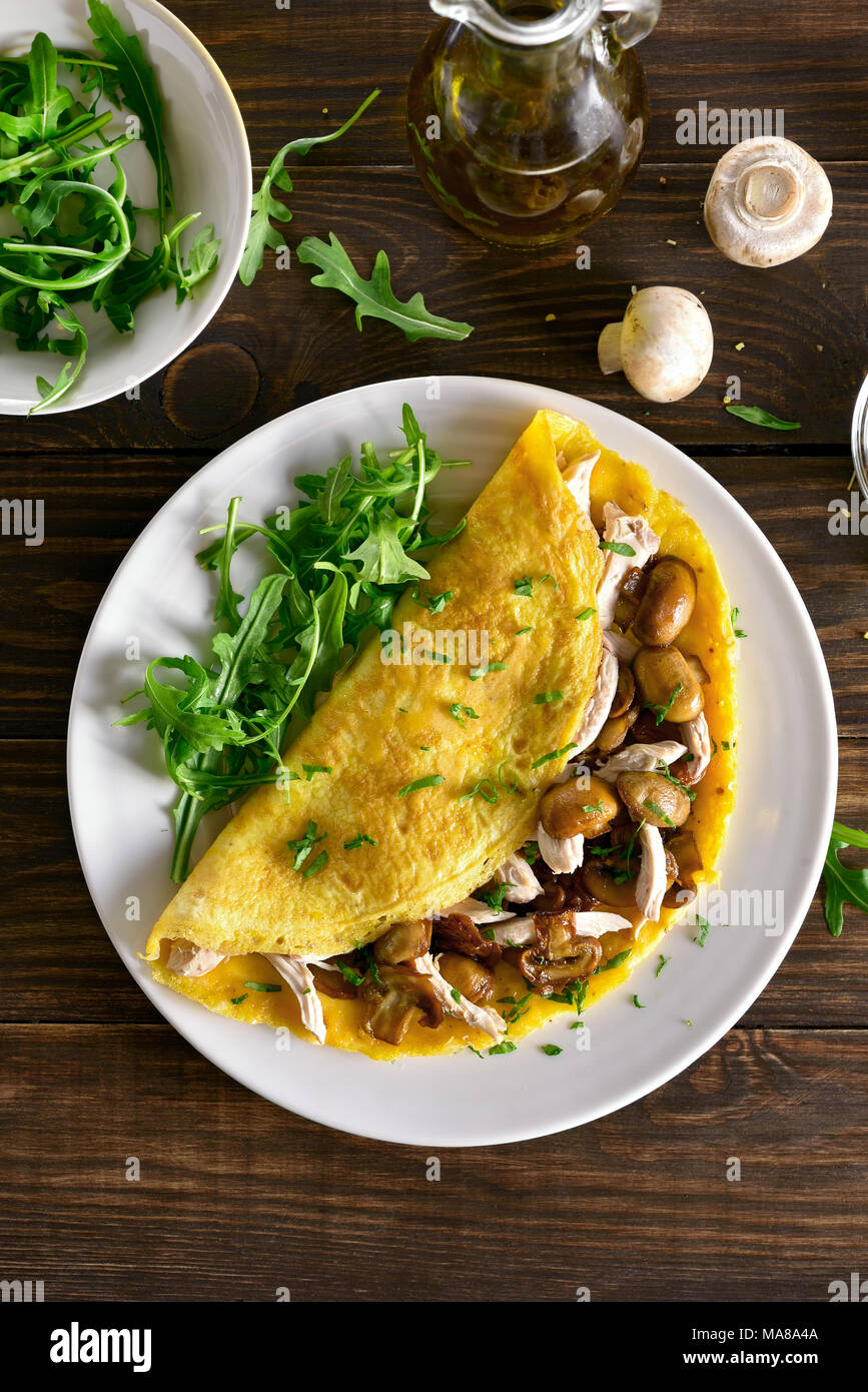 Omelette with mushrooms, chicken meat, greens on wooden table. Healthy food for breakfast. Top view, flat lay - Stock Image