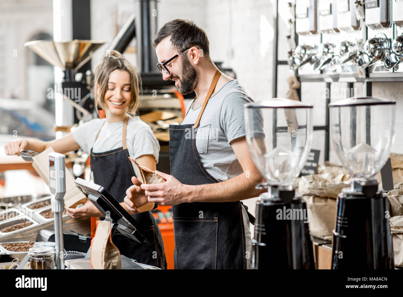Two sellers in uniform filling bags with coffee beans working in the coffee store - Stock Image