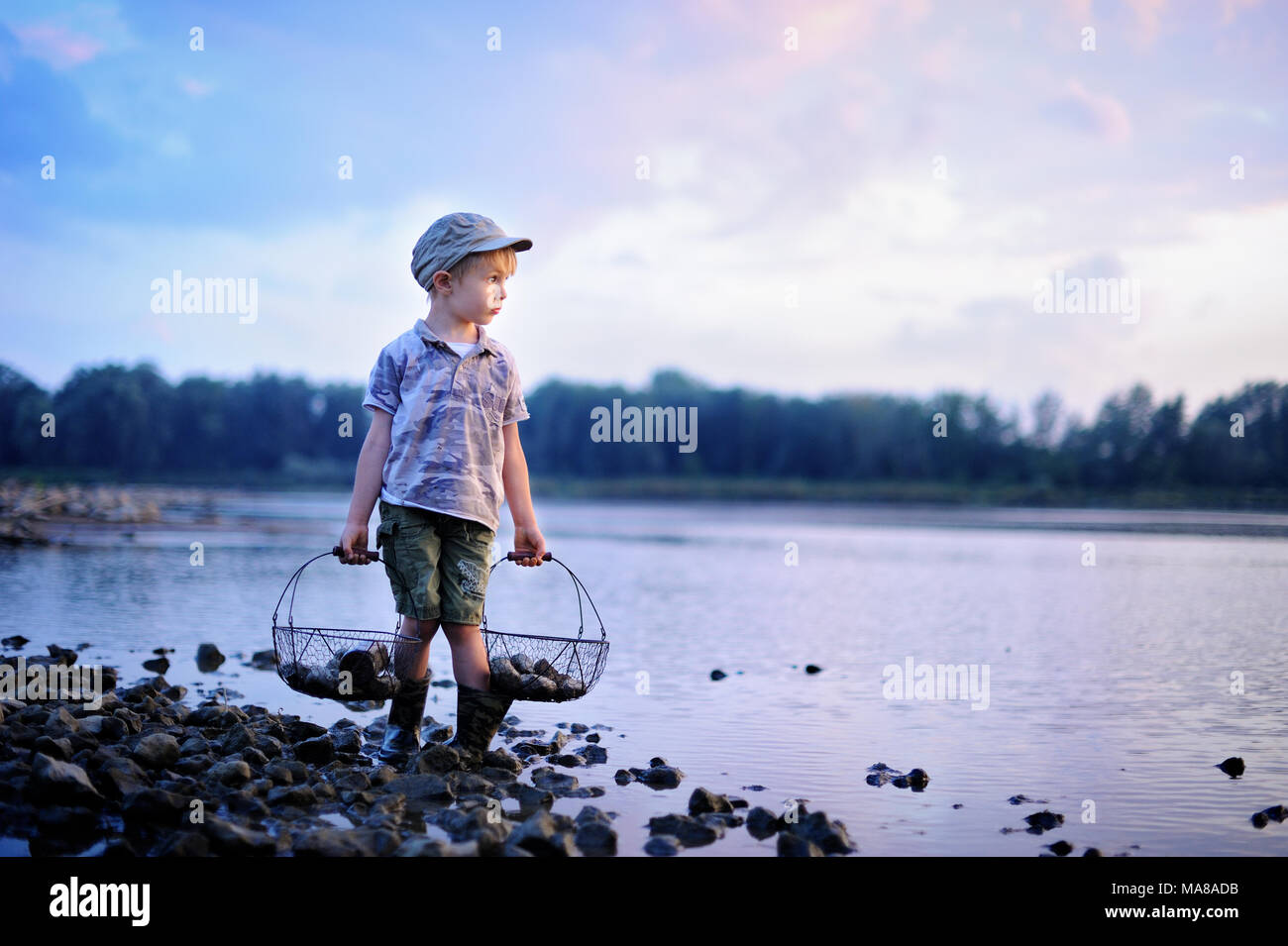A little boy is playing on the bank of the summer river. - Stock Image
