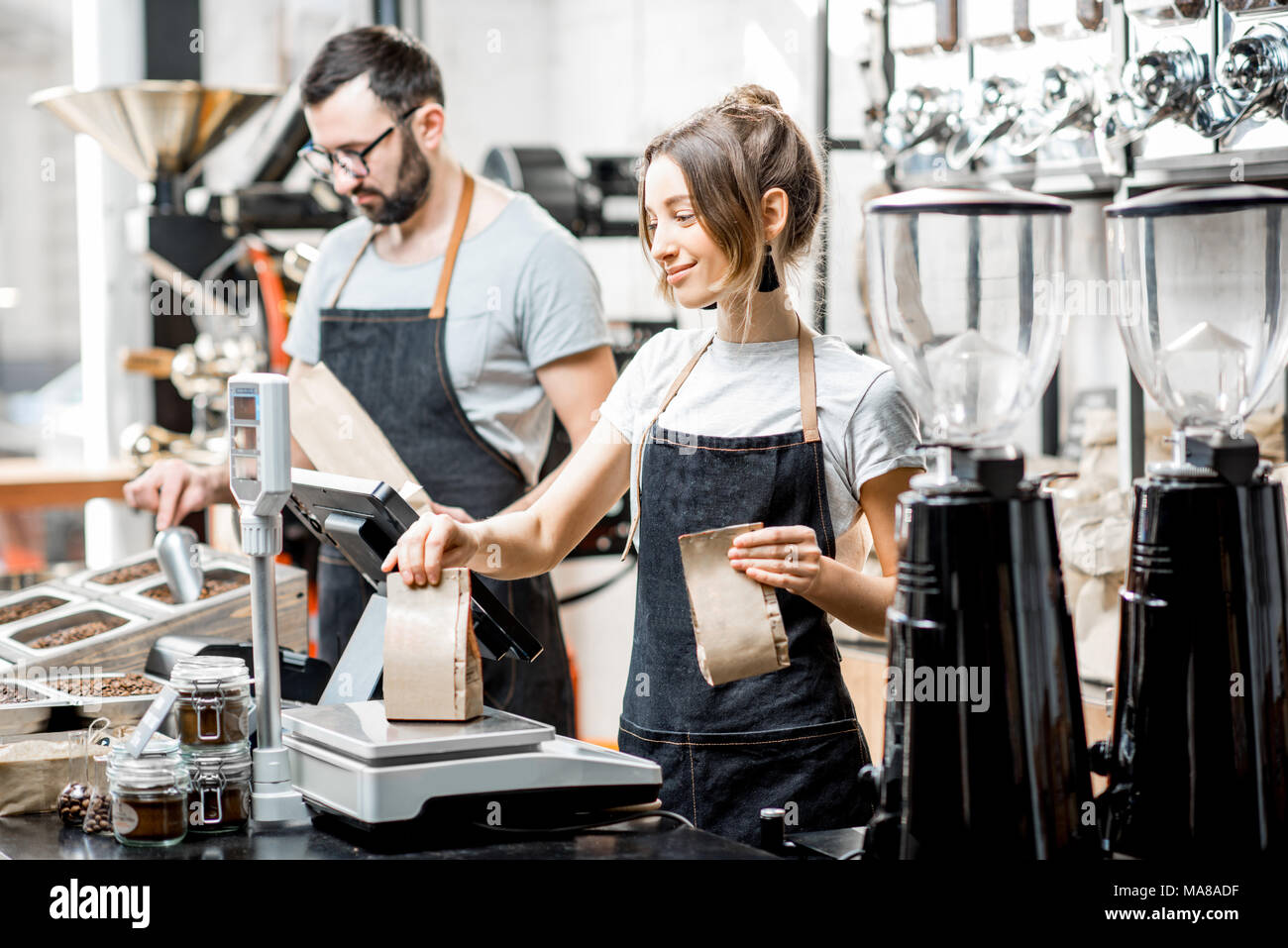 Two sellers in uniform weghing bags with coffee beans working in the coffee store - Stock Image