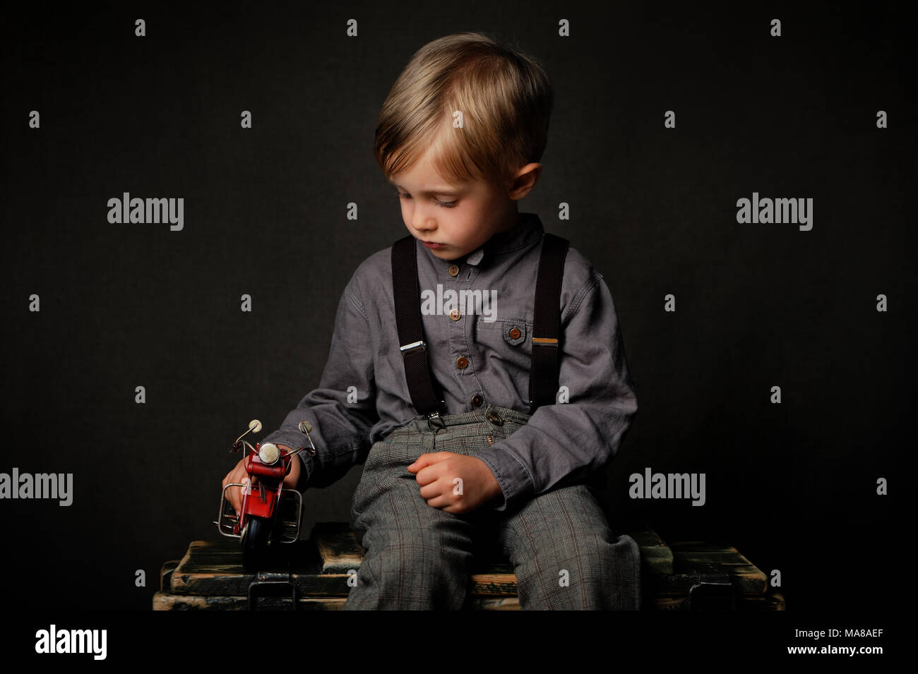 A  four years old sad  boy is sitting on the chest in studio and looking sideways at the motorcycle toy. - Stock Image